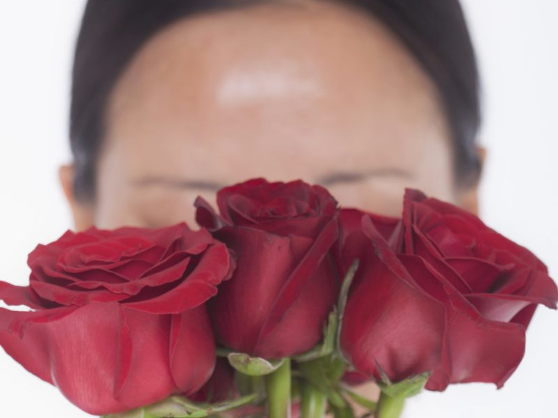woman with rosacea hiding face behind red roses